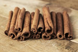 Stack of cinnamon wrapped with a rope over a wooden surface