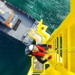Man climbing on wind turbine offshore - Learn about coatings for sustainable resources