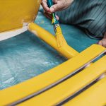 woman painting a chair with yellow paint - Structure and Behavior of Wetting Agents
